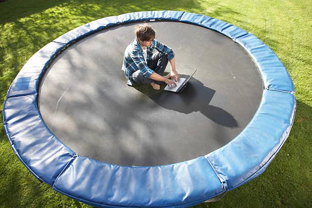 junger mann entspannen auf trampolin mit laptop - gartentrampolin stock-fotos und bilder