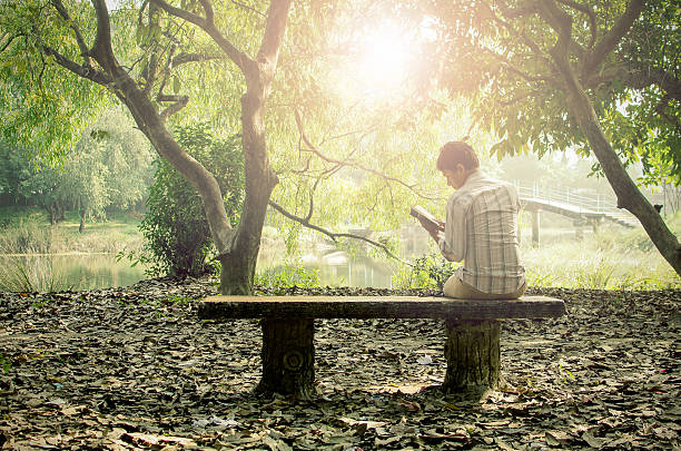 Young man relaxing & reading books alone stock photo