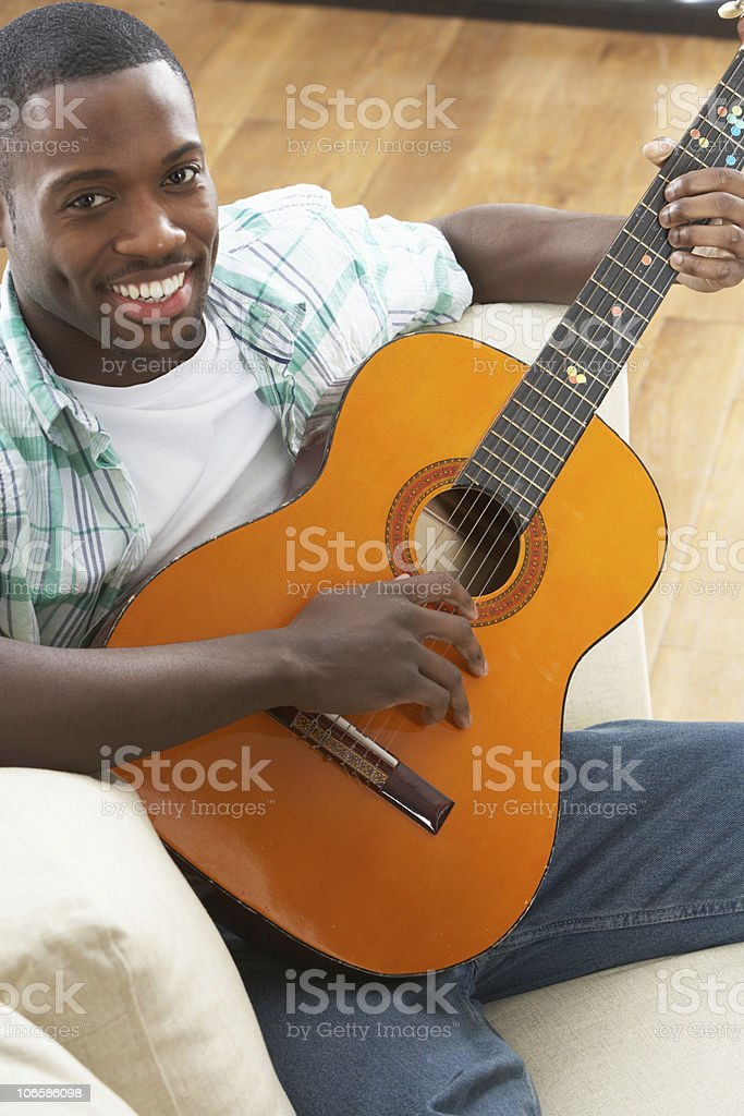 Young Man Relaxing Sitting On Sofa Playing Acoustic Guitar royalty-free stock photo