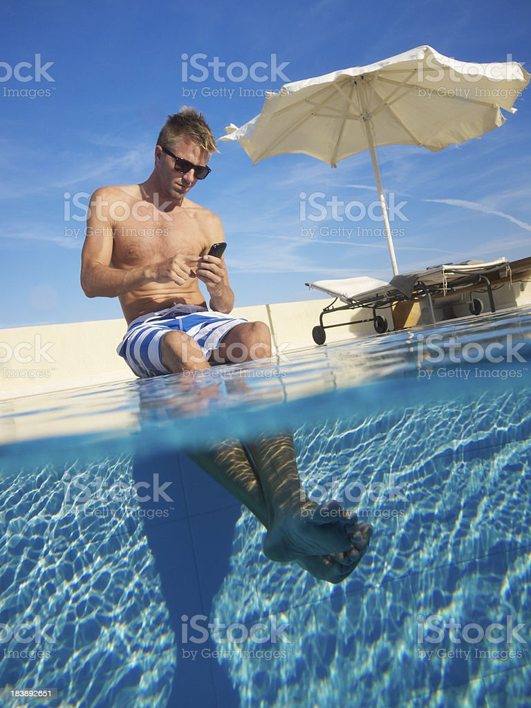 Young Man Relaxing Texting on Smartphone Feet in Swimming Pool royalty-free stock photo