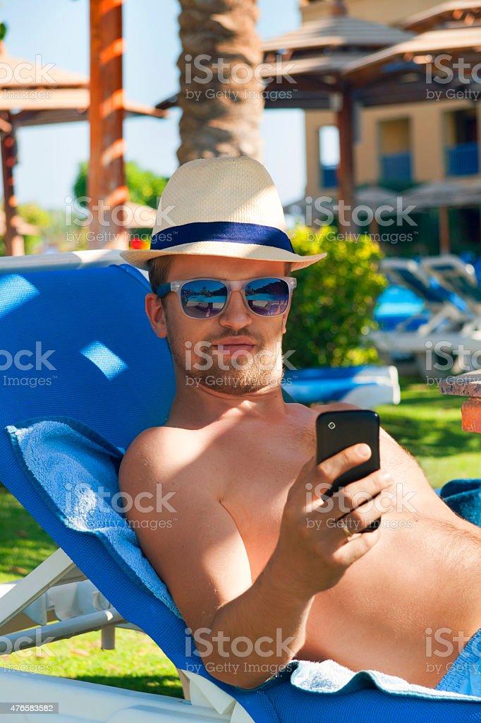 Młody człowiek relaksujący, wysyłanie SMS-ów na Smartphone stopy basen – zdjęcie