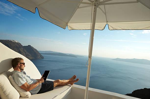 junger mann entspannend mit tablet pc am meer mit balkon - sonnenschirm terrasse stock-fotos und bilder