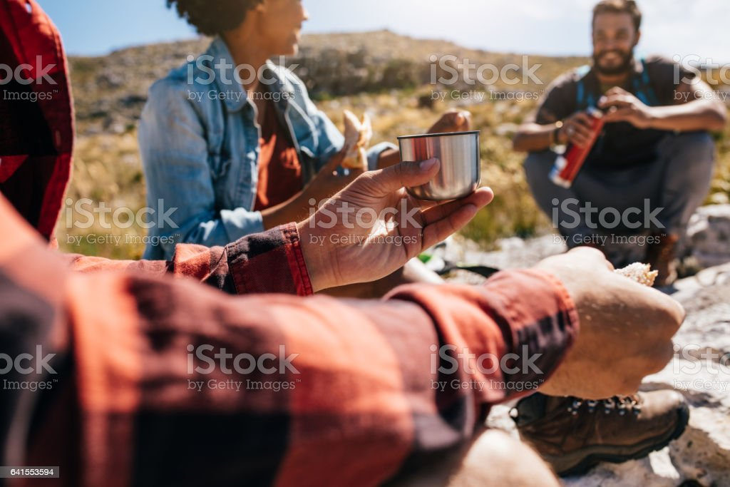 Young man relaxing with friends during a hike stock photo