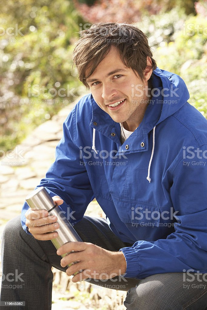 Young Man Relaxing With Thermos Flask In Autumn Landscape royalty-free stock photo