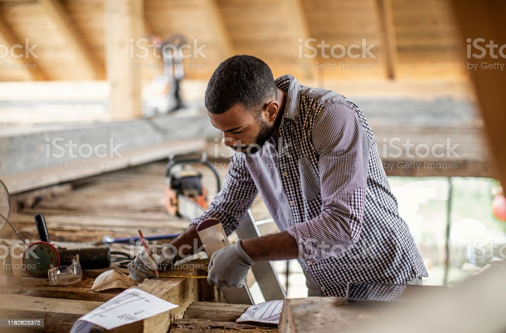 Young Man Renovating the Attic Young Man Renovating the Attic Adult Stock Photo