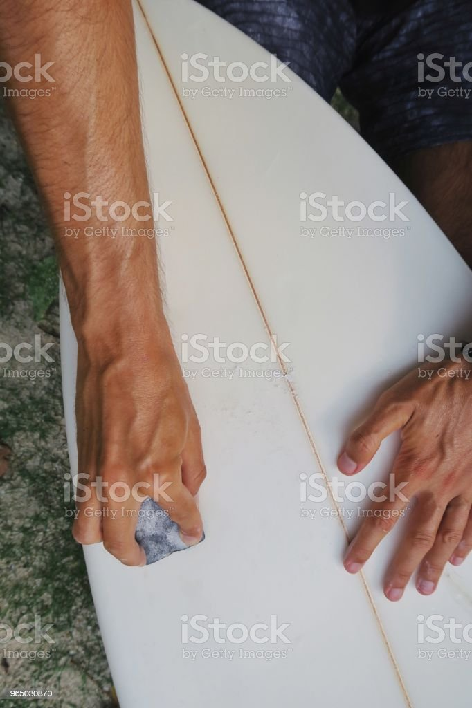 Young man repairing his surfboard on the beach royalty-free stock photo