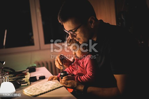 Young man repaIring photo lens with cute little daughter