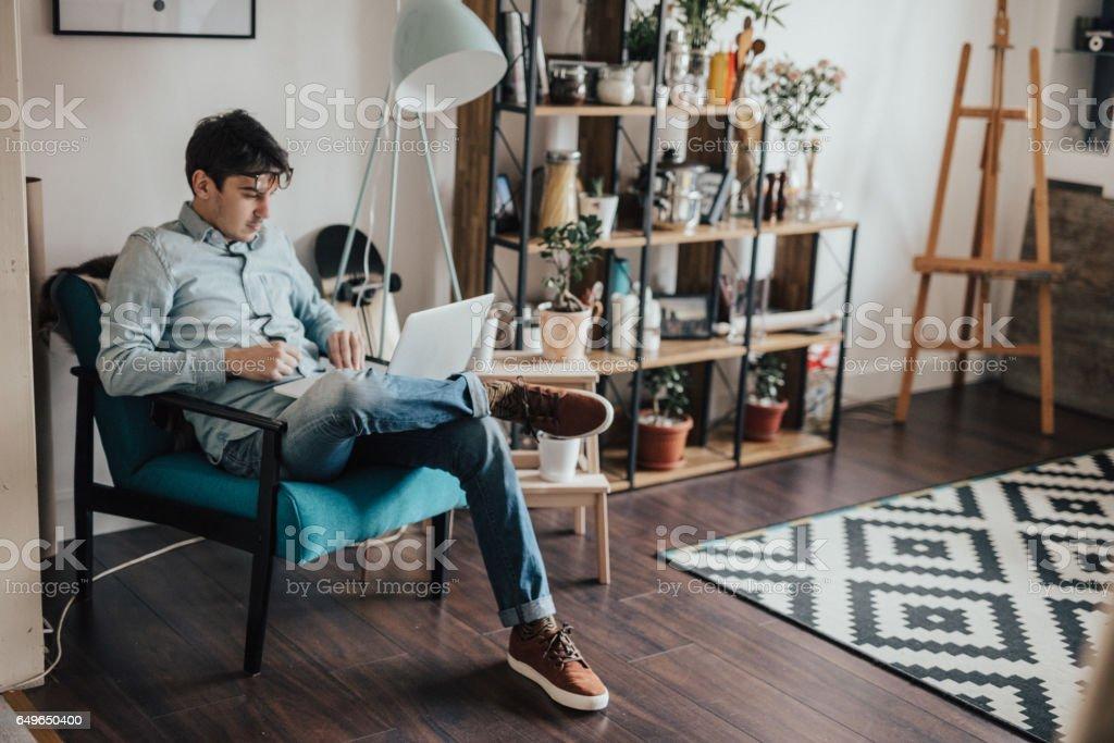 Meu jovem, descansando em sua casa e usando o laptop - foto de acervo