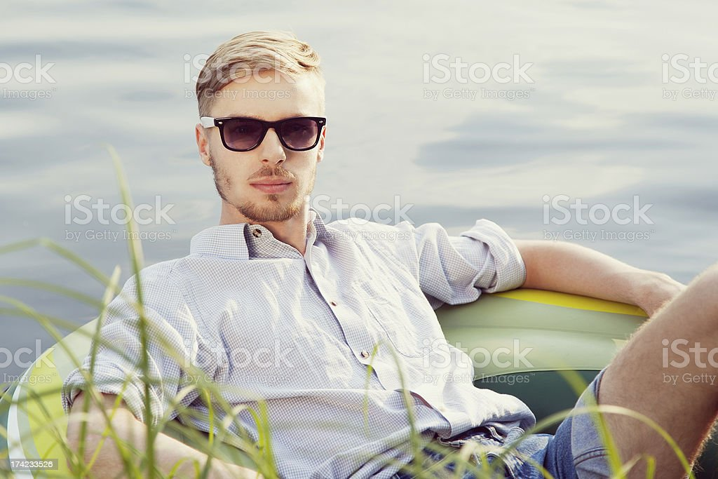 Young man resting in boat stock photo