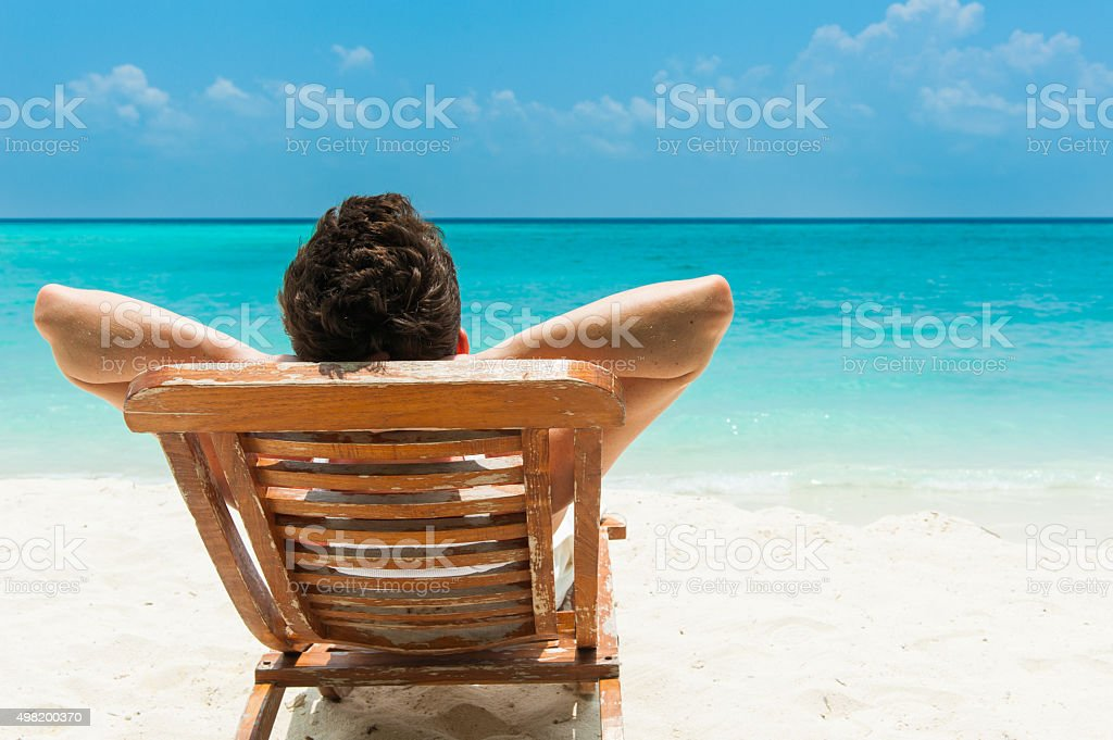Young man resting on beach Man relaxing on beach, ocean view, Maldives island 2015 Stock Photo