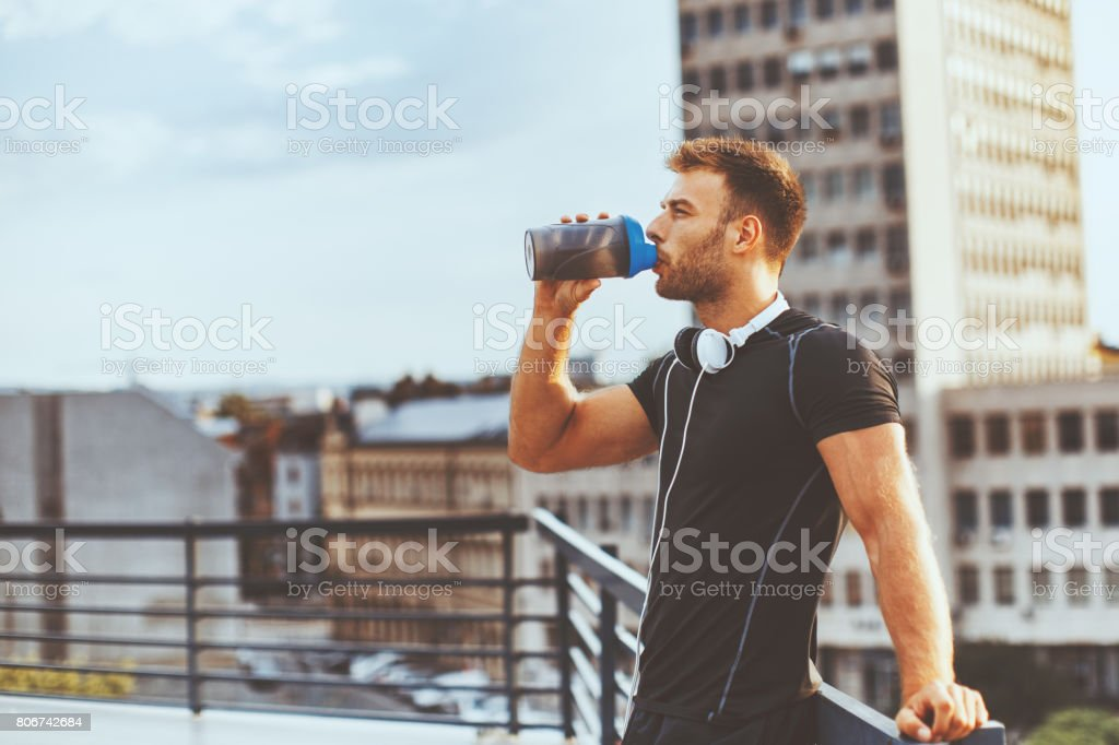 Young man resting on the roof of the building after workout and drink water stock photo