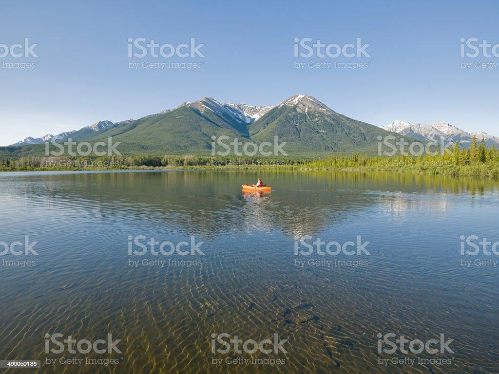 Young man rests while paddling kayak on mountain lake stock photo