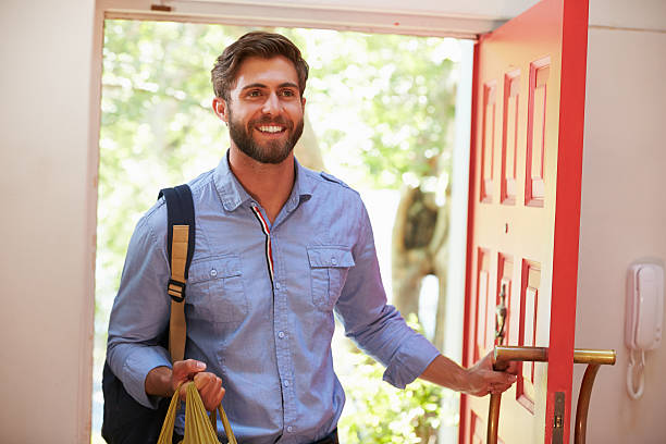young man returning home for work with shopping - terugkomen stockfoto's en -beelden