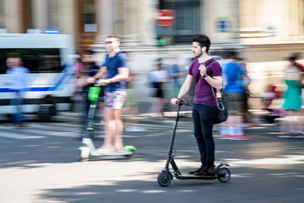 a young man rides an electric scooter at high speed in the streets of paris, france. - electric push scooter stock photos and pictures