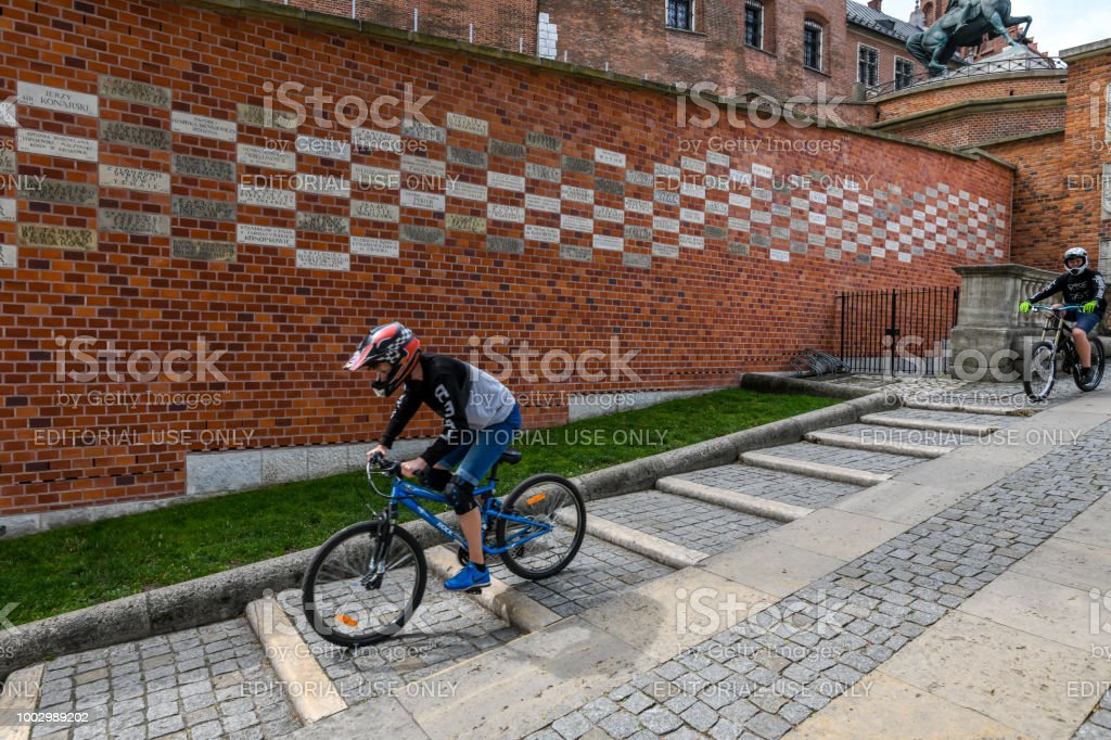 Young man rides down steps outside in old town Krakow, Poland stock photo