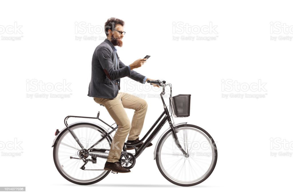 Young man riding a bicycle and looking at his phone stock photo