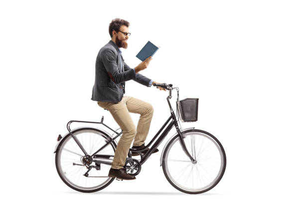 Young man riding a bicycle and reading a book stock photo