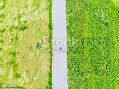 969439086 istock photo Young man riding a bicycle on a road 969439072
