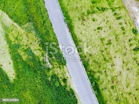 969439086 istock photo Young man riding a bicycle on a road 969439084