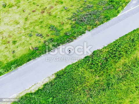 969439086 istock photo Young man riding a bicycle on a road 969439092