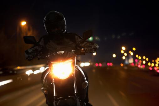 Young Man riding a motorcycle at night