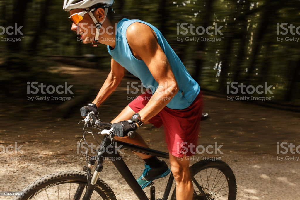 Young man riding a mountain bike on old country road.Spring season. stock photo