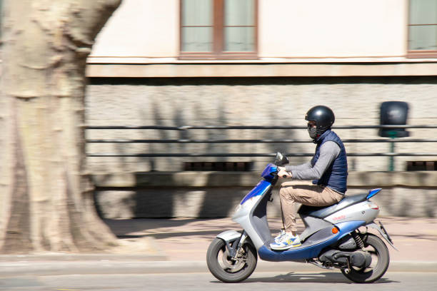 A young man riding a scooter motorbike on city street