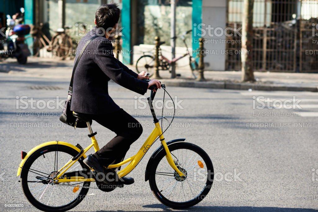 Jeune homme monté sur un vélo Ofo - Photo