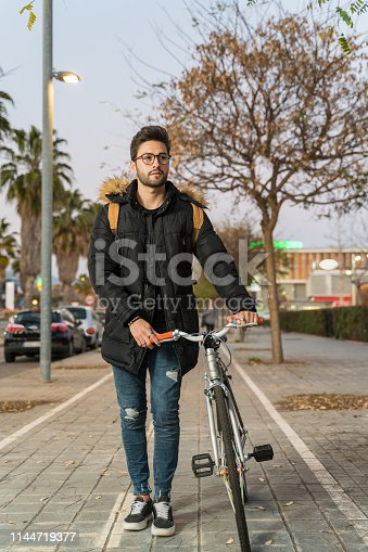 Young man riding bike in city street in winter at sunset.