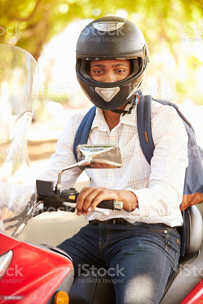 Young Man Riding Motor Scooter To Work stock photo