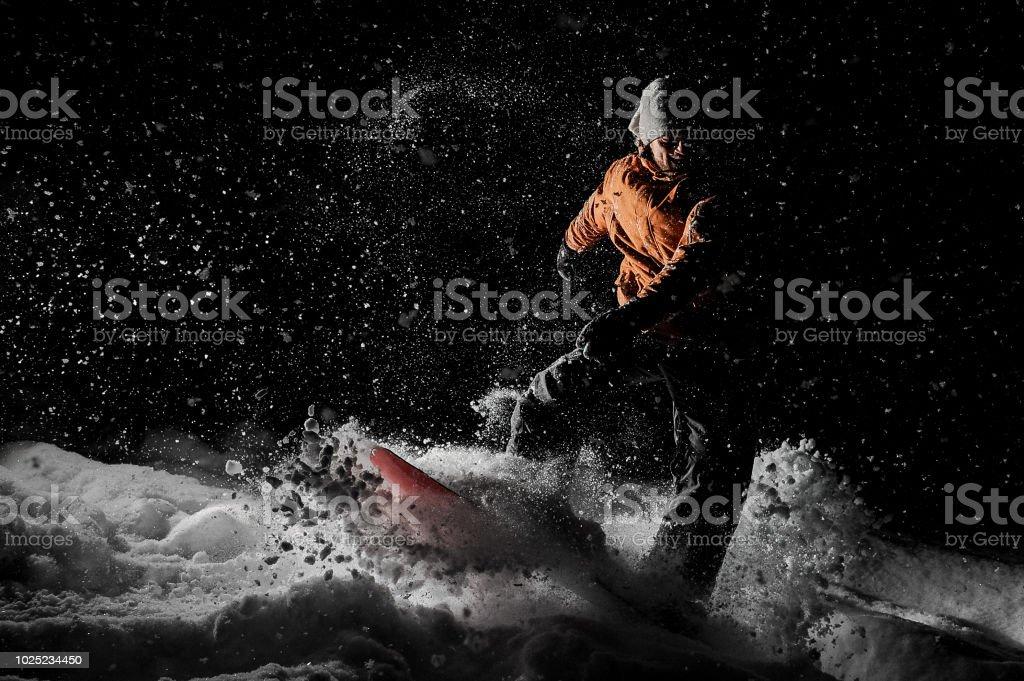 Junger Mann reitet auf dem Snowboard im Höhenkurort in der Nacht – Foto