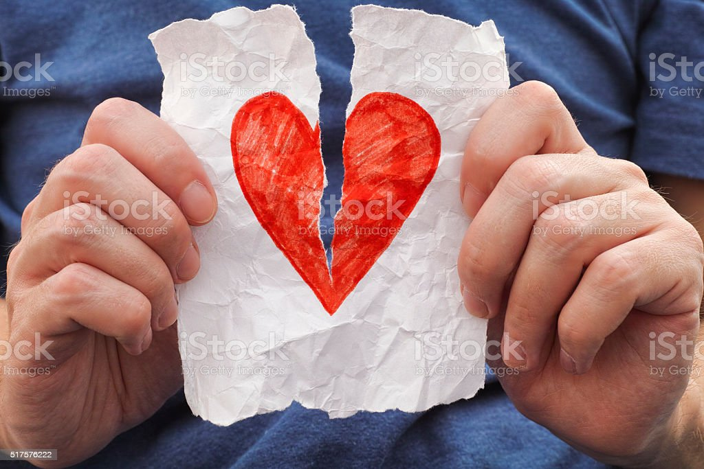 Young man ripping red heart on a piece of paper. stock photo