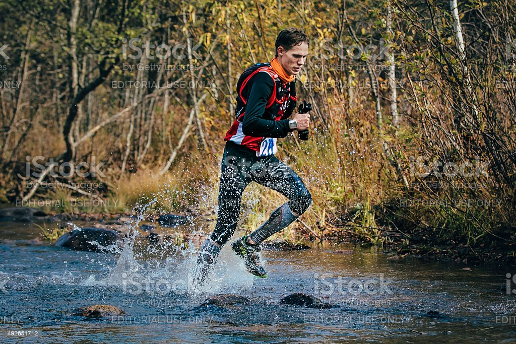 Young man runner splash water in river, during crossing river stock photo
