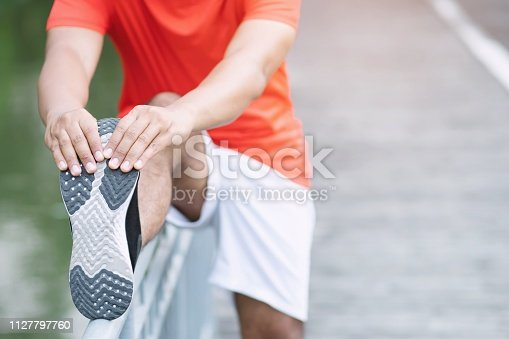 young man runner stretching for warming up before running or working out on road in the park. Track and Field Athlete exercise. Fitness and sport healthy lifestyle concept.
