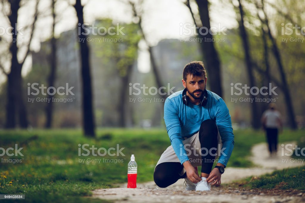 Young man runner tying shoelaces stock photo