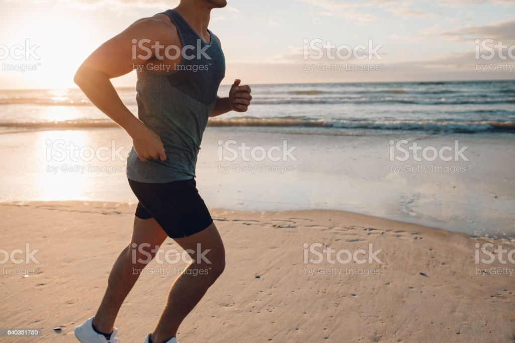 Young man running along the beach in morning stock photo