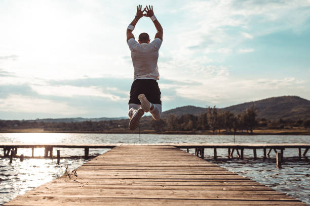 Young man running and jumping at the dock of a lake stock photo