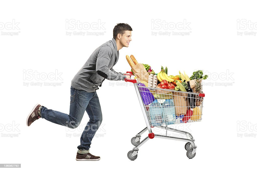 Young man running and pushing a shopping cart stock photo