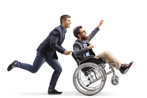 Young man running and pushing an excited man in a wheelchair gesturing with hand stock photo