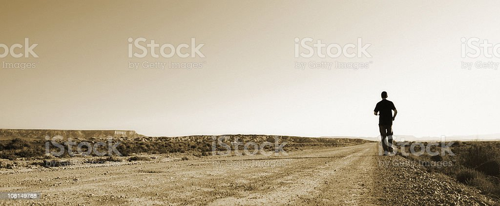Young Man Running Down Road in Desert, Sepia Toned stock photo