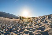 Young man running down sand dunes at sunset enjoying vacations and being playful