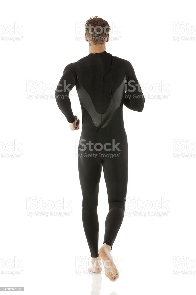 Young man running in wet suit royalty-free stock photo