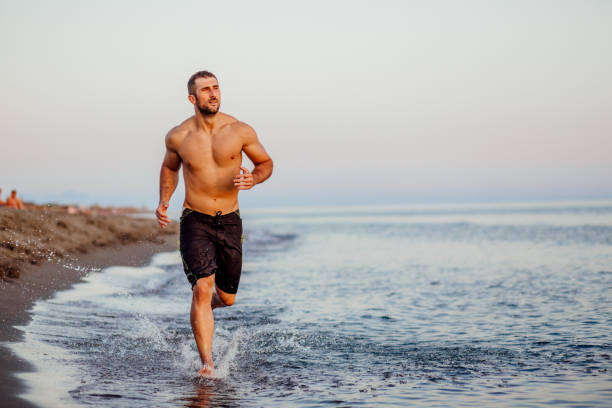 Young man running on a beach stock photo