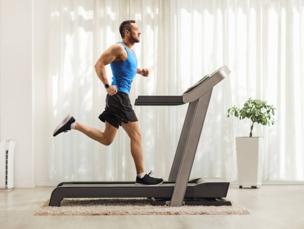 Young man running on a treadmill at home Full length profile shot of a young man running on a treadmill at home treadmill stock pictures, royalty-free photos & images