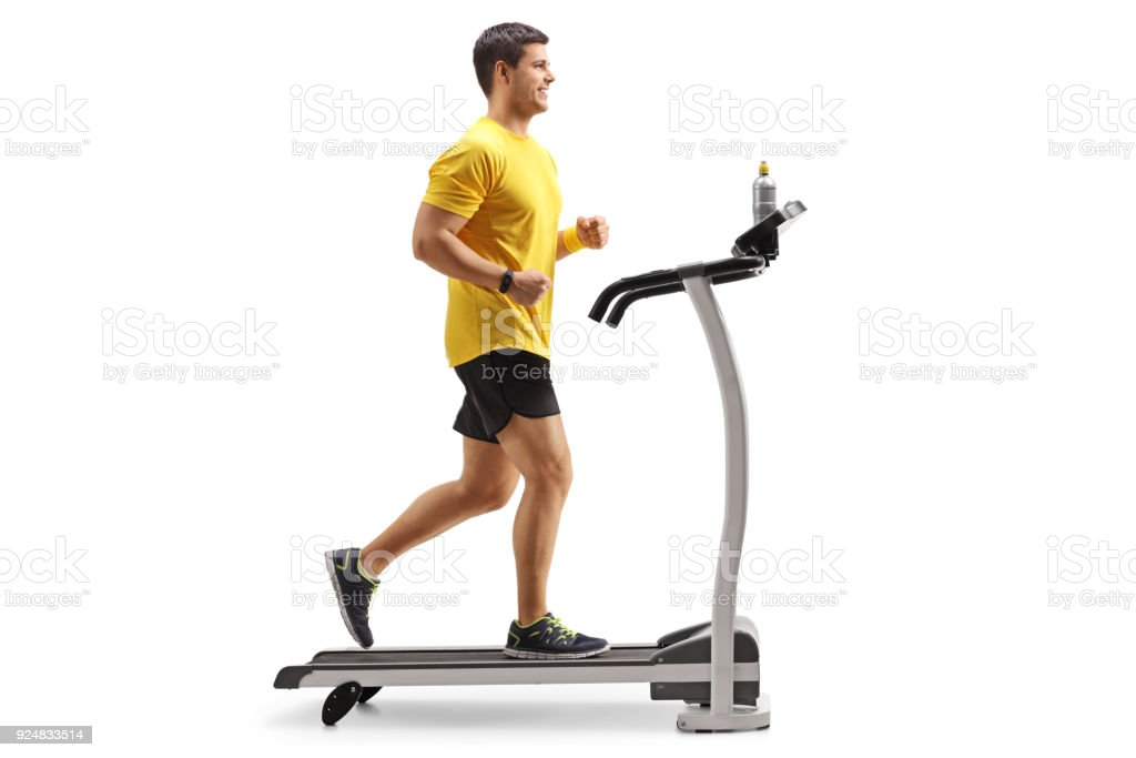 Young man running on a treadmill stock photo
