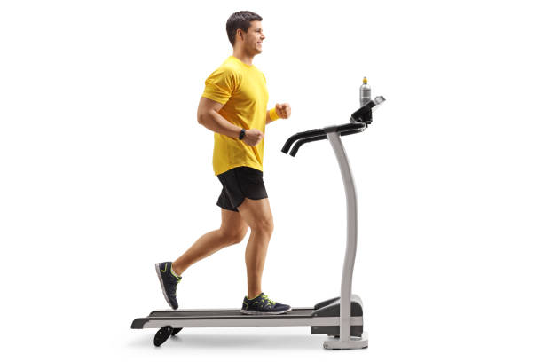 young man running on a treadmill - treadmill stock photos and pictures