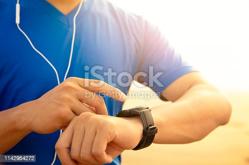 young Man running on beach and checking Heart Rate Monitor On watch