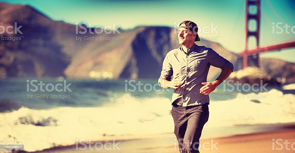 Young man running on San Francisco under Golden Gate royalty-free stock photo
