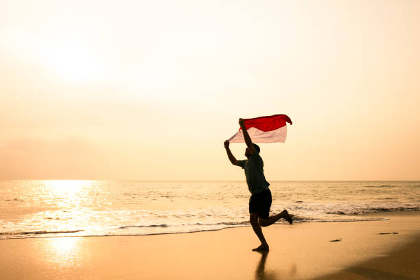 young man running on the  beach carrying Indonesia flag stock photo