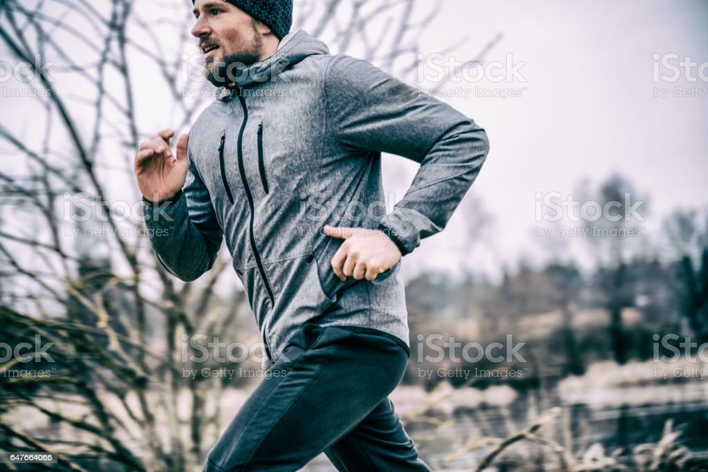 Young man running on the field stock photo